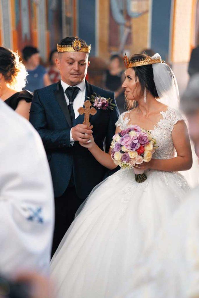 Mireasa a purtat o rochie alba cu trena si un voal de 3 m, iar mirele a fost imbracat intr-un costum de ceremonie de culoare albastra.